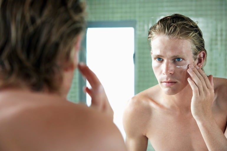 man looking in mirror under eye cream and protection